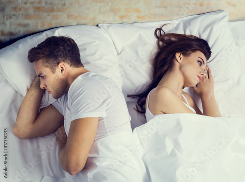 Canvastavla Picture of unhappy young attractive couple on the bed in bedroom