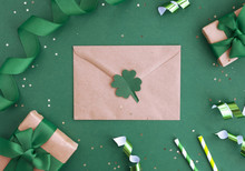 St Patricks Day Composition. Envelope, Gift Boxes, Clover And Festive Decor On A Green Background. Sale And Discount Concept. Top View, Flat Lay