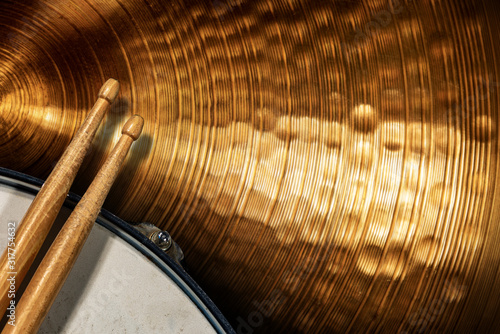 Fotografia Close-up of two wooden drumsticks on an old metallic snare drum and golden colored cymbal with copy space