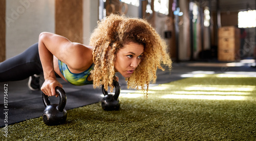 Focused woman working out with weights on a gym floor Tapéta, Fotótapéta