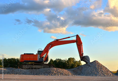 Photo Excavator loads of stone and rubble for processing into cement or concrete for construction work and reuse