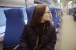 girl sits on a train / winter transport, one adult girl sits by the train window traveling