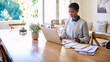 Leinwanddruck Bild - Focused young African American female entrepreneur working from home
