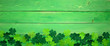 Leinwanddruck Bild - St Patricks Day banner with bottom border of shamrocks. Overhead view over a green wood background. Copy space.
