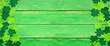 Leinwanddruck Bild - St Patricks Day banner with double side border of shamrocks. Top view over a green wood background. Copy space.
