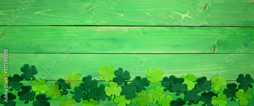 Fototapeta St Patricks Day banner with bottom border of shamrocks. Overhead view over a green wood background. Copy space. obraz