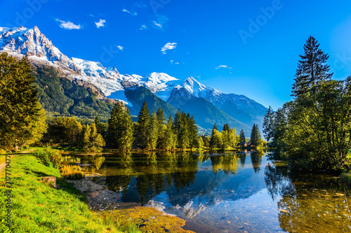 Obraz  The lake reflects the forest and the blue sky - fototapety do salonu