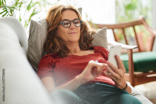 Obraz na plátne Smiling mature woman lying on her couch using a cellphone