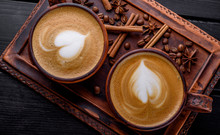 Two Cups Of Cappuccino Coffee With Latte Art On Dark Background