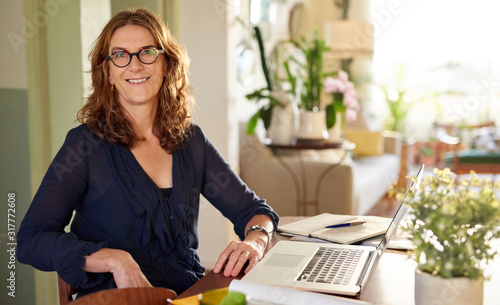 Fototapeta Smiling mature female entrepreneur working at her dining table