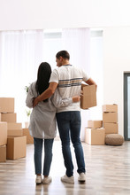 Couple In Room With Cardboard Boxes On Moving Day