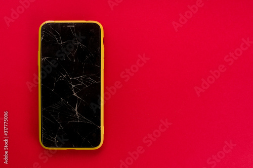 Fotomural Smartphone with broken screen on red background