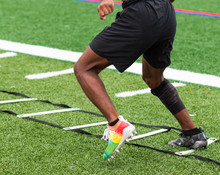 Athlete Running Ladder Drills On Turf Field In Cleats