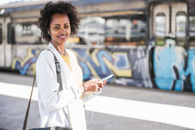 Portrait Of Smiling Young Woman With Cell Phone And Earphones At The Train Station