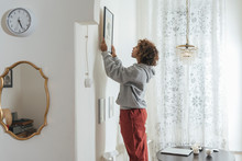 Young Woman Hanging Up Picture...