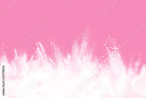 White powder explosion isolated pink background.