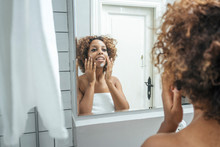 Young Woman In Bathroom Applyi...