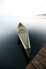 A Sleek Canoe Tied To A Dock On A Tranquil Pond In Maine.