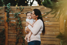 Mid-30's Mom Holding And Kissing Baby Girl In Backyard Near Fence