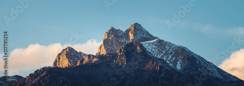 A panoramic view of a mountain peak illuminated by golden rays. - 317785254