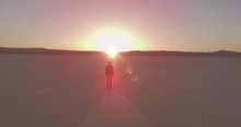 Guy Wearing Torn Jeans And A Hat Stands In The Lowland With The Sun Rising In The Background.