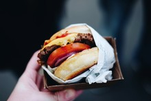 CLOSE-UP OF HAND HOLDING Hamburger
