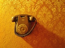 CLOSE-UP OF TELEPHONE OVER YELLOW WALL