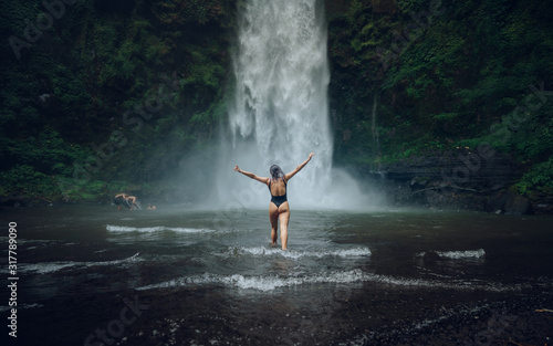 Fototapety, obrazy: Beautiful girl in a black swimsuit enjoys a magnificent tropical waterfall. Female tourist. Ecotourism concept image travel girl