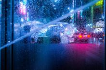 Close-Up Of Wet Window In Illuminated City At Night During Rain