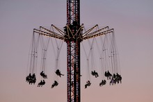 People On Amusement Park Ride Against Clear Sky