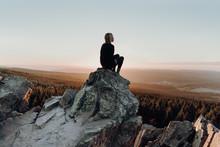 Woman Sitting On Rock Against Landscape