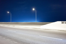 Empty Road Against Clear Blue Sky At Night