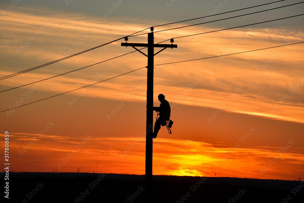 Fototapeta Lineman on pole during sunset
