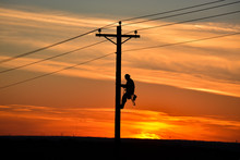 Lineman On Pole During Sunset