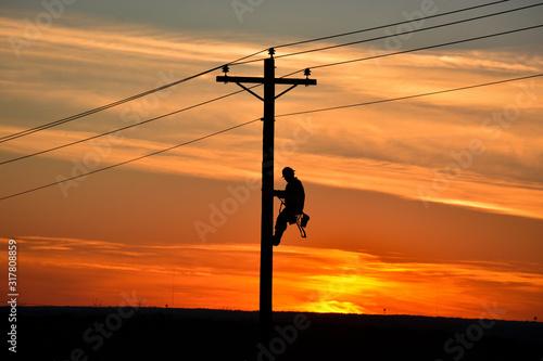Slika na platnu Lineman on pole during sunset