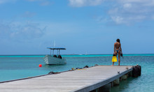 Beautiful Blue Crystal Clear Beach. Fishing Boat Pier, Girl Getting Ready To Snorkel/spearfish/dive.