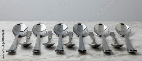 Cucharas plateadas de varios tamaños, acomodadas sobre una superficie de marmol Canvas Print
