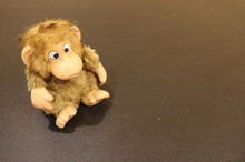 A Toy Monkey With Slanting Eyes Sits On The Black Surface On The Left And Looks At The Lower Right Corner.