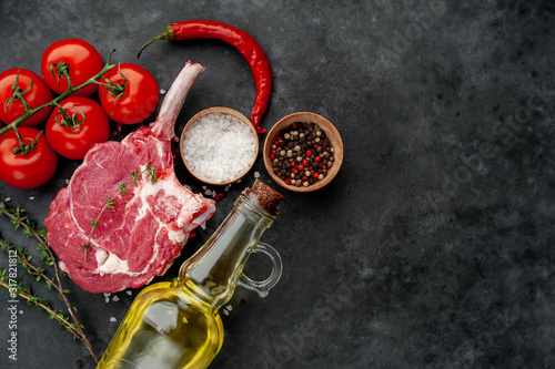 Fototapeta raw beef steak, beef tomahawk with spices, tomatoes, sunflower oil, thyme on a stone background. with copy space for your text obraz