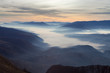 Soft, abstract, moody view of a valley filled with thick morning fog, colorful sunrise sky and impressive mountains