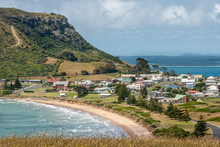 Stanley, Tasmania, Australia - December 15, 2009: The Town At The Base Of The Nut Volcanic Plug. Beach And Surf. Cloudscape And Blue Ocean With Mountains In Back.