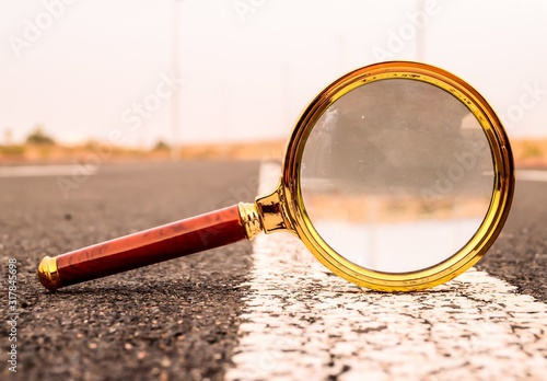 Closeup shot of a magnifying glass on a road street with a blurred background Wallpaper Mural