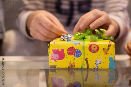 Closeup shot of a man opening a yellow gift with a green and silver ribbon with a blurry background