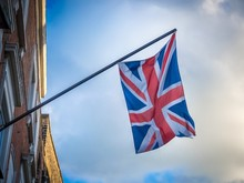 Low Angle Shot Of A British Flag Waving In A Balcony Under A Cloudy Sky