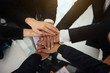 Unity and teamwork concept. Close up top view of young business people putting their hands together. Stack of hands in office.