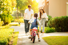 Daughter Train To Ride A Bicycle From Her Moter And Her Father