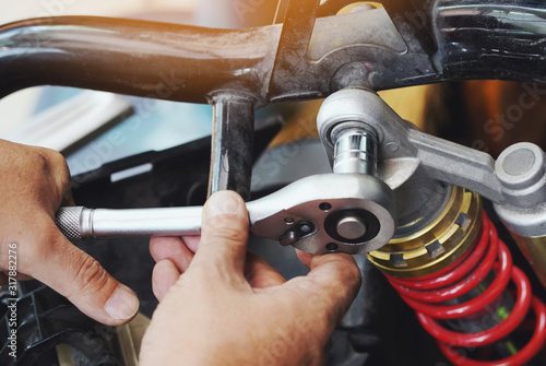 motorcycle Mechanic using impact wrench socket Replace rear shock absorber on big scooter in garage,check and repair or Maintenance motorcycle concept Canvas Print