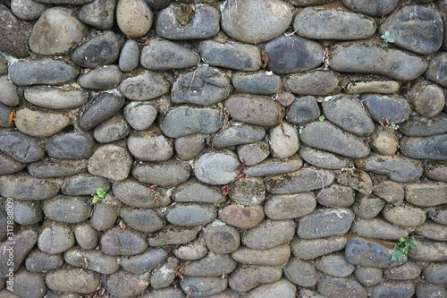 Horizontal stone wall built with smooth round river rocks set in mortar