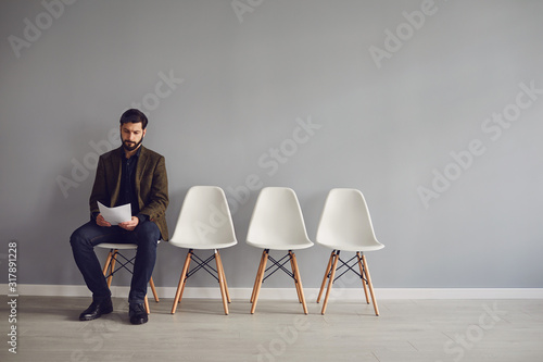 Worker awaits interview sitting on a chair in the room. Canvas Print