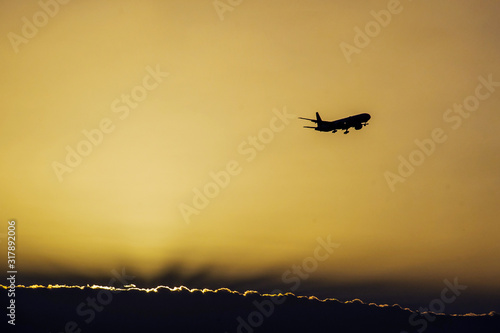 Photo Jet plane landing in sunrise time in front of dramatic sky.